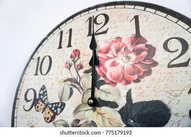 Close-up vintage clock hanging on white wall shows twelve o'clock