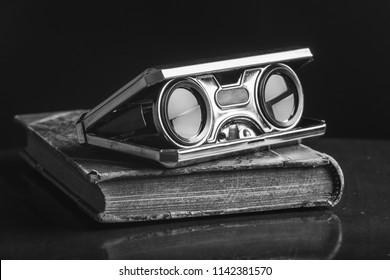 Closeup vintage folding opera glasses. Old compact binoculars.