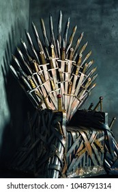 Closeup vintage image of a swords throne at textured studio wall background.