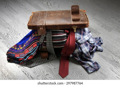 close-up of vintage leather suitcase, crowded on a variety of things on the background of gray flooring studio