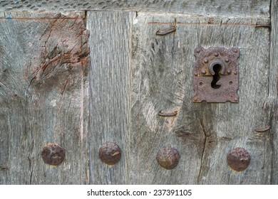 Closeup of vintage run-down wooden door and rusty iron lock