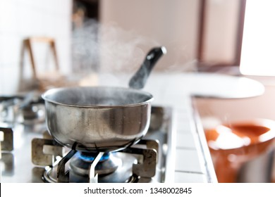 Closeup of vintage tiled gas stove top with tiles white countertop and stainless steel pot and steam cooking with blue flame in retro kitchen
