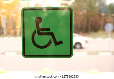 Closeup of vinyl green sign for places for disabled in the bus. Green vynil sign for disabled people of green color on the bus glass.