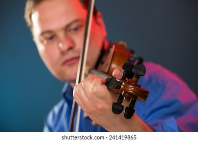 Close-up of violin in the hands of the violin virtuoso with a face out of focus.