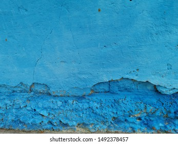 closeup of vivid bring colourful blue wall showing signs of weathering and damage