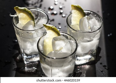 Closeup vodka in a glass with ice, lime.  Gin, tonic, tequila