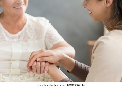 Close-up of volunteer's hand taking care of senior person