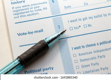 Closeup of 'Vote-by-mail' section on a voter registration form, with ballpoint pen laying on the form, pointing toward the 'Yes' checkbox.