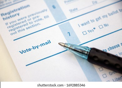 Closeup of 'Vote-by-mail' section on a voter registration form, with ballpoint pen laying on the form.