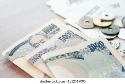 Closeup: Wads of Japanese banknotes 500, 1000, 10000 yen and small coins with sale slips from the convenience store lay on the table. Japan, Tax free for tourist, Cost of living, Expenses, Tokyo 2020.