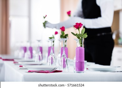 Close-up Of Waiter Arranging Roses In Vase On Wedding Table