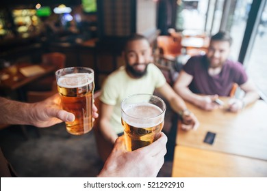Closeup of waiter bringing two glasses of beer for two smiling bearded men sitting in pub