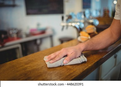 Close-up of waiter cleaning counter with cloth at cafe