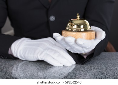 Close-up Of A Waiter Hand Holding Service Bell