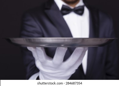 Close-up of a waiter holding an empty silver tray against dark background