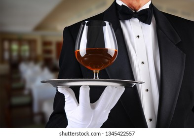 Closeup of a waiter in a restaurant with a brandy snifter on a serving tray.