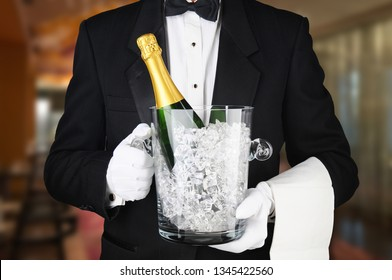 Closeup of a waiter in a restaurant carrying an ice bucket with a bottle of unopened champagne.