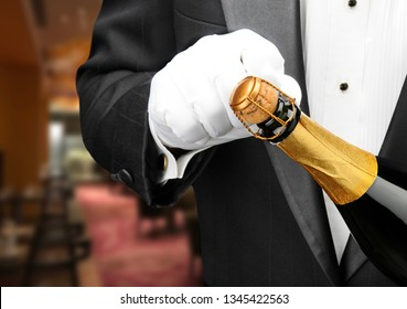 Closeup of a waiter in a restaurant opening a bottle of champagne.