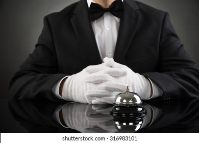 Close-up Of Waiter Sitting At Desk With Service Bell