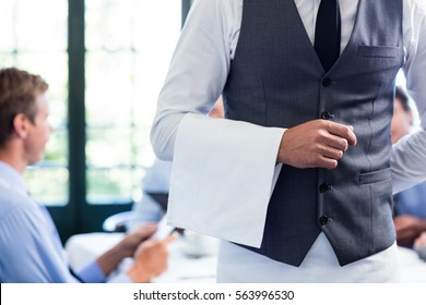 Close-up of waiter standing with napkin in restaurant