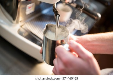 Close-Up of waiter steaming milk at the coffee machine in restaurant