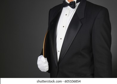 Closeup of a waiter in a tuxedo holding a serving tray under his arm. Horizontal format on a light to dark gray background. Man is unrecognizable.