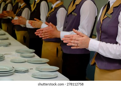 Close-up of waiters clapping hands. Seminar concept.