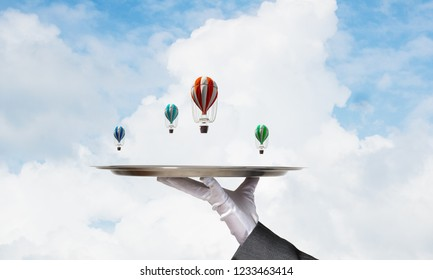 Closeup of waiter's hand in glove presenting flying aerostats on metal tray with blue cloudy skyscape on background. 3D rendering.