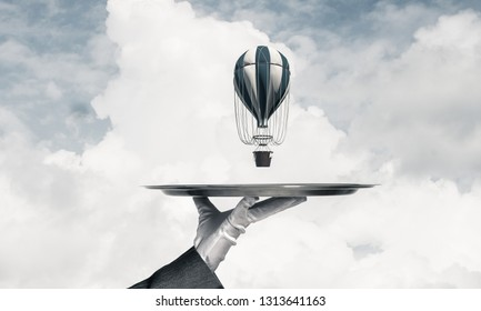 Closeup of waiter's hand in glove presenting flying aerostat on metal tray with blue cloudy skyscape on background. 3D rendering.