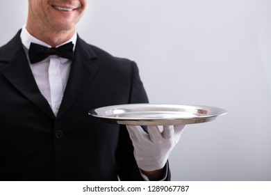 Close-up Of Waiter's Hand Holding Empty Silver Tray Against White Background