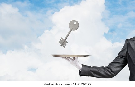 Closeup of waiter's hand in white glove presenting stone key symbol on metal tray with blue cloudy skyscape on background. 3D rendering.