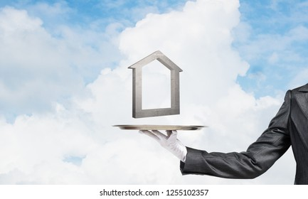 Closeup of waiter's hand in white glove presenting stone house symbol on metal tray with blue cloudy skyscape on background. 3D rendering.