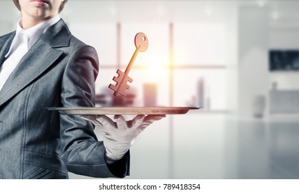 Closeup of waitress's hand in white glove presenting stone key symbol on metal tray with office view on background. 3D rendering.