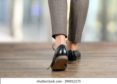 Close-up of  walking woman feet in black shoes on the floor