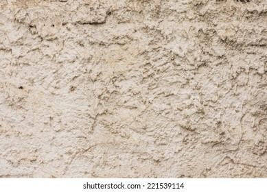 Close-up to a wall with irregular and messy plaster and white paint.