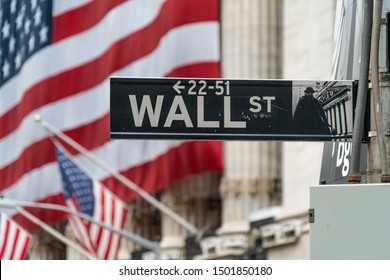Closeup Of Wall St. Street Sign And Large New York City Financial Institution In Background With American Flag. The Most Economically Powerful City And The Leading Financial Center Of The World.