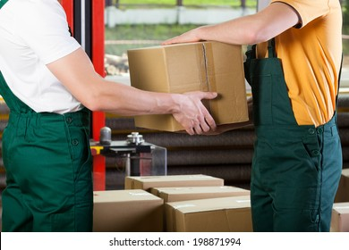 Close-up of warehouse workers with box, horizontal