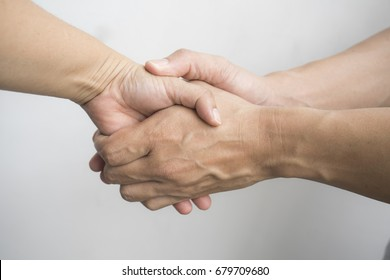 Closeup of warm hand shaking between Asian woman and man  with white background.