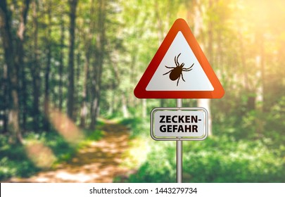 close-up of warning sign with text ZECKEN GEFAHR, German for beware of ticks, against defocused forest background