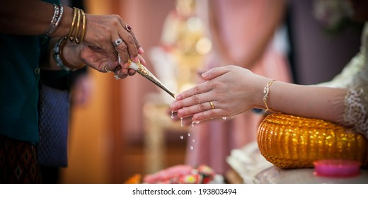 Close-up of water being poured on the hands of the bride during a traditional Thai wedding ceremony.