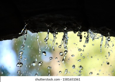 close-up of water droplets from stone arch blur background