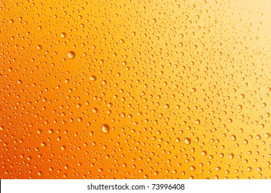 Close-up of water drops on textured metallic surface as background.