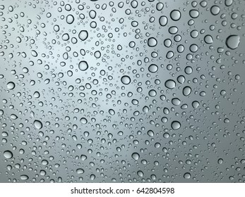 Close-up of water drops from rainy  on glass surface as background with light from outdoor.