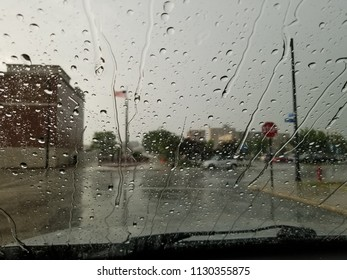Closeup of water drops & rivulets of water on a windshield during a Summer rainstorm. Wet pavement, street signs, fire hydrant, lampposts, flagpole, trees, buildings & cars in the distance.