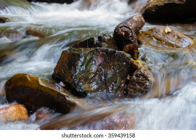Closeup of water flowing around rocks with motion blur