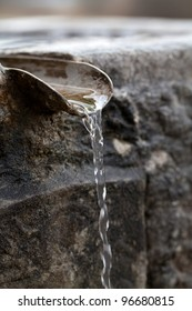 Closeup of water running from outdoor wall faucet