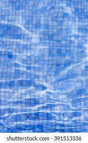Close-up of water in swimming pool with blue tiled floor. From above