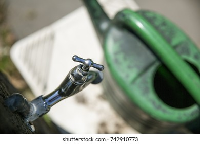 close-up of a water tap or faucet with a green watering can in the background out of focus