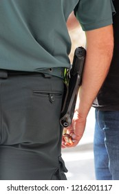 close-up of the weapon of a policeman wearing a pistol in a belt holster, rear view