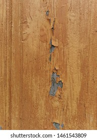 closeup of weathered and pealing dull gold coloured paint on natural wood door